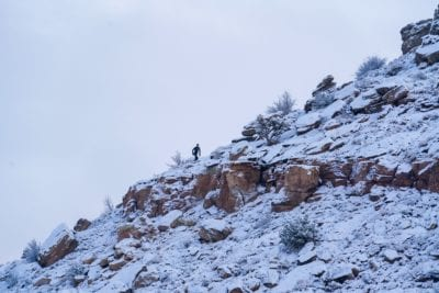 A trail runner climbs the snow covered Curt's Lane trail in the Lunch Loops.