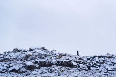 A trail runner crosses a rocky ridge covered in snow in the Lunch Loops trail system.