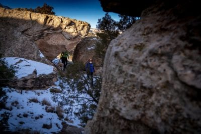 Women and dogs slip through the keyhole feature in the Lunch Loops trail system near Gran Junction, Colorado