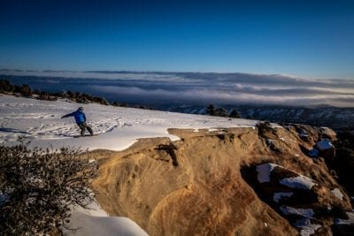 Master snowboarder Robbie Drake cuts a hard turn at the edge of a desert cliff on The Ribbon mountain bike trail above Grand Junction, Colorado.