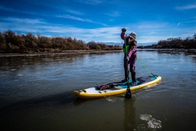 Elizabeth Fortushniak paddles in the Colorado River on a January day with ice in the water and a blue sky above.