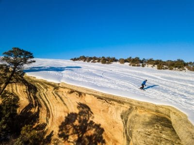 Snowboarding along the cliff edge of the desert mountain bike trail, The Ribbon, with a rare blanket of snow.
