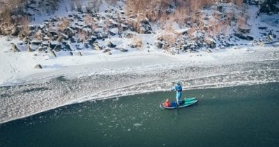 An aerial photo of a man paddling through the ice along a frozen edge of the Colorado River